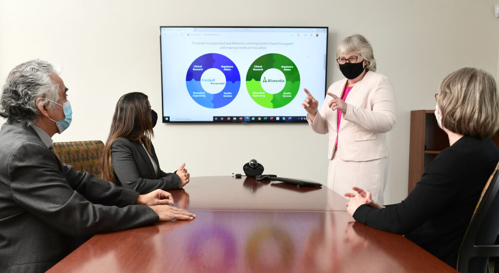 conference room, woman wearing a face mask, standing gesturing at slides on screen, 3 others look on