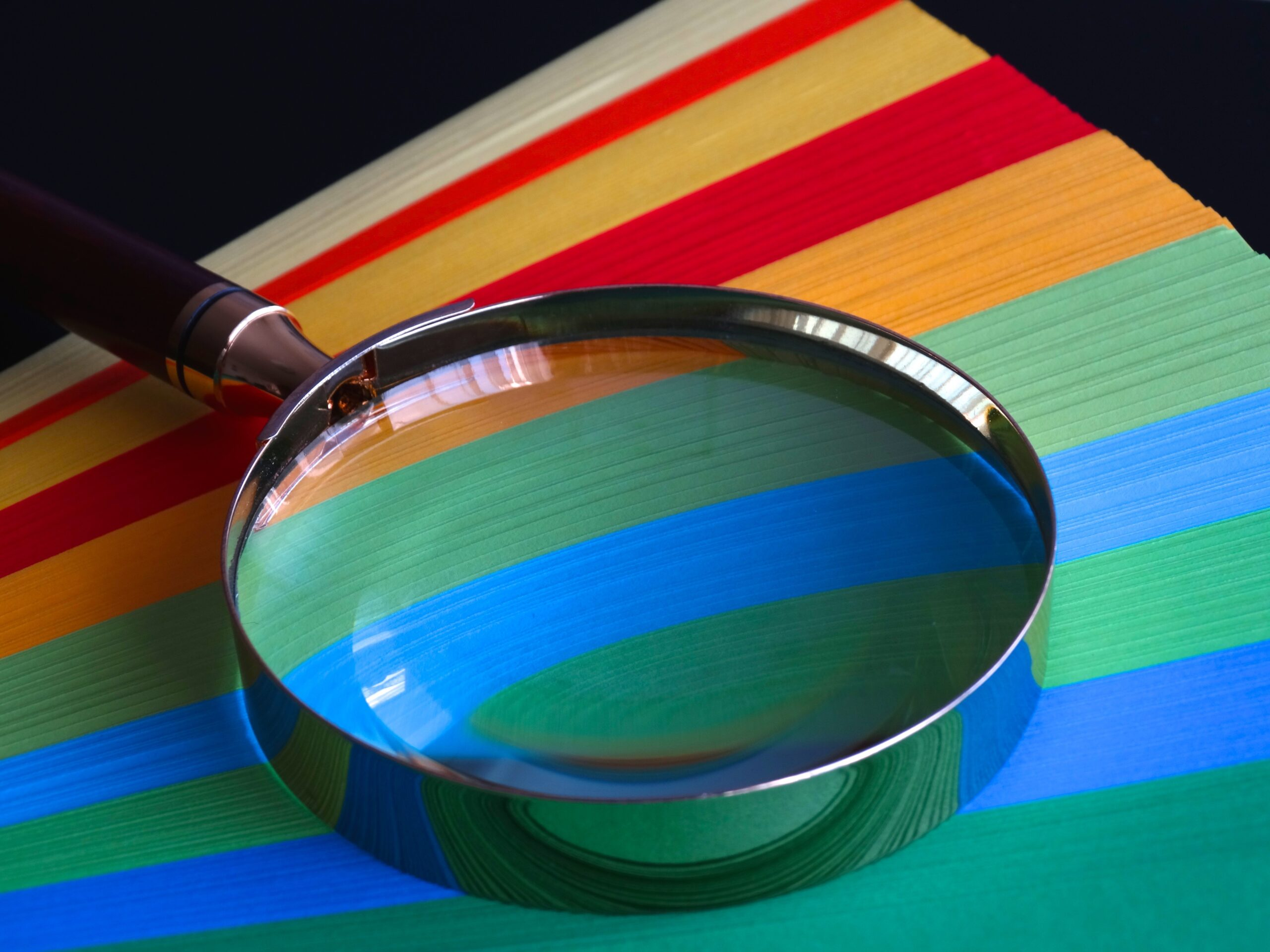 magnifying glass on top of colorful papers