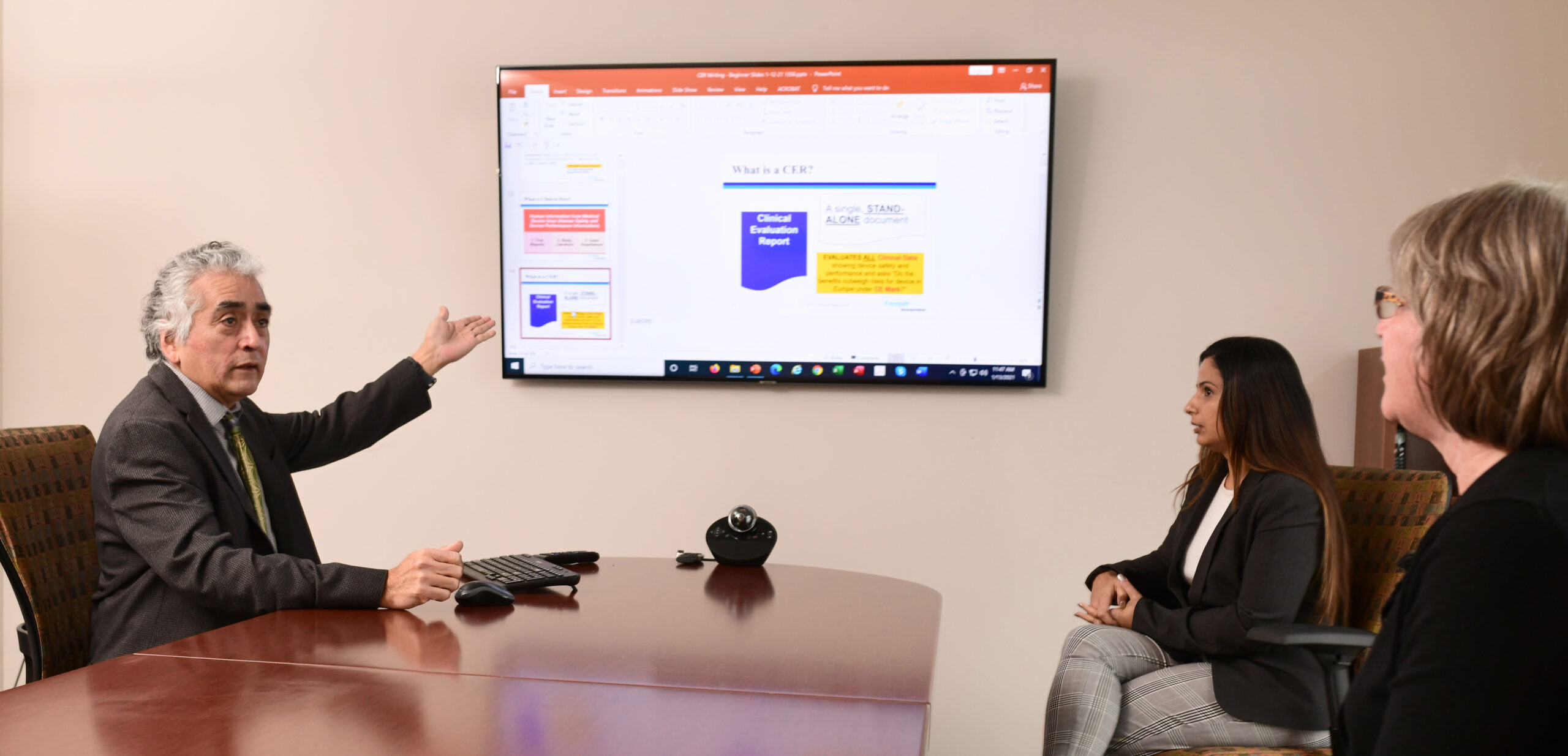 Conference room, person gesturing to slide on a screen, 2 people watch