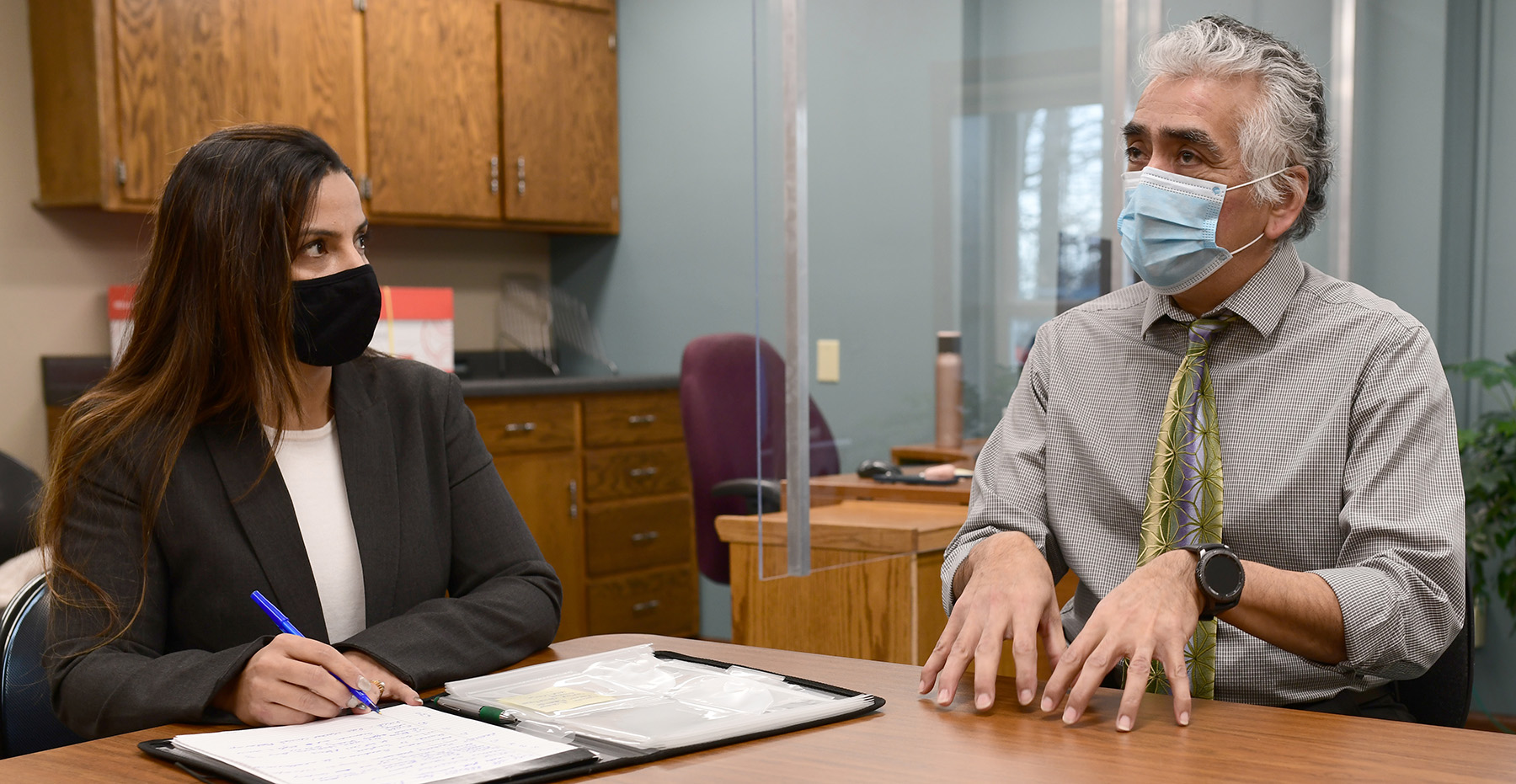 Two people at a table, wearing face masks, one gesturing with hands, other writing on paper