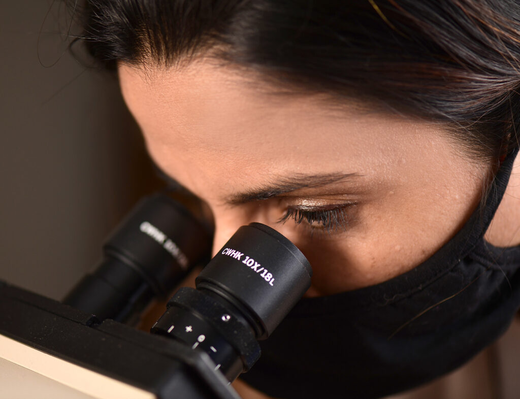 woman wearing a face mask looking into microscope