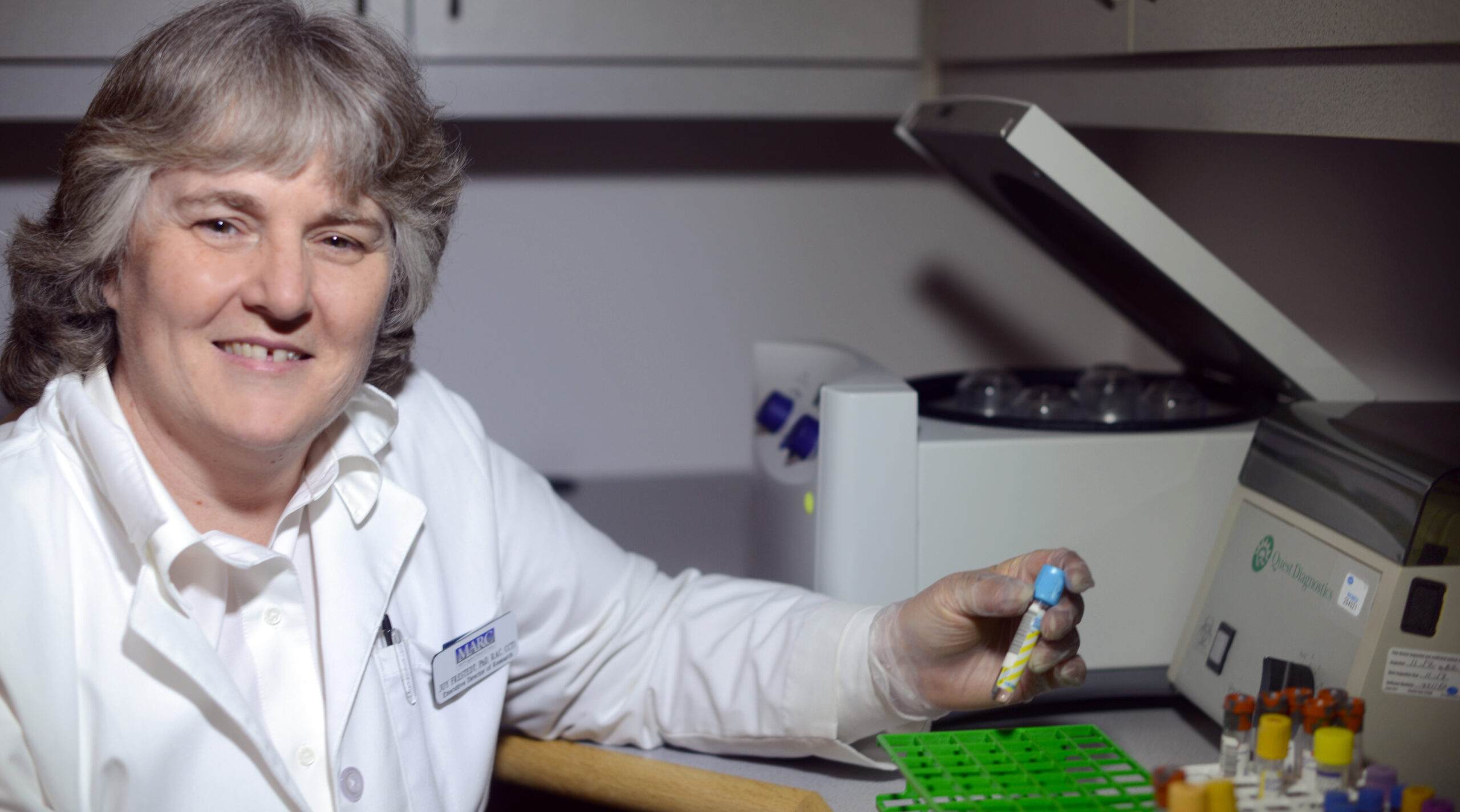 Dr. Joy Frestedt, smiling and holding a test tube in a lab