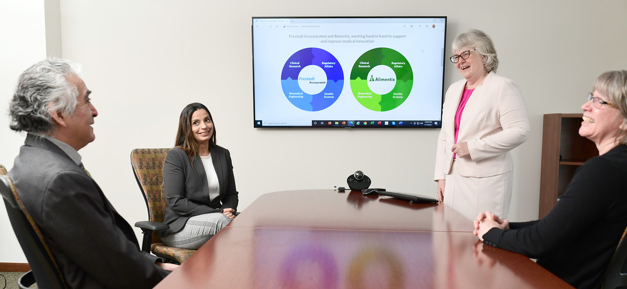 4 people in conference room table smiling, slide on screen behind them